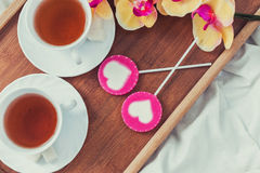 Πρόγευμα στο κρεβάτι στην ημέρα βαλεντίνων Φλυτζάνι του τσαγιού και των γλυκών καραμελών Έννοια αγάπης ή διακοπών Στοκ Εικόνα