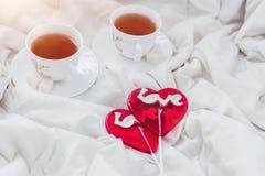 Πρόγευμα στο κρεβάτι στην ημέρα βαλεντίνων Φλυτζάνι του τσαγιού και των γλυκών καραμελών Έννοια αγάπης ή διακοπών Στοκ Φωτογραφία