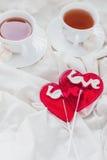 Πρόγευμα στο κρεβάτι στην ημέρα βαλεντίνων Φλυτζάνι του τσαγιού και των γλυκών καραμελών Έννοια αγάπης ή διακοπών Στοκ φωτογραφίες με δικαίωμα ελεύθερης χρήσης