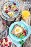 Πρόγευμα την ημέρα του βαλεντίνου - τηγανισμένα αυγά και ψωμί με μορφή μιας καρδιάς και φρέσκων λαχανικών στοκ εικόνες
