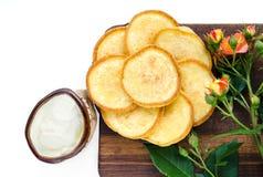 Πρόγευμα της ημέρας αδείας - χρυσές τηγανίτες με την ξινή κρέμα Ένας ξύλινος πίνακας, ένα ροδαλό λουλούδι Άσπρο υπόβαθρο, τοπ άπο Στοκ Εικόνα