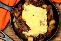 Πρόγευμα του Τέξας Skillet με την μπριζόλα, την πατάτα και το αυγό Στοκ Φωτογραφία