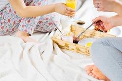Πρόγευμα Mom και κορών στο κρεβάτι σε ένα άσπρο κάλυμμα Στοκ Φωτογραφίες