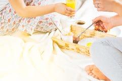 Πρόγευμα Mom και κορών στο κρεβάτι σε ένα άσπρο κάλυμμα Στοκ εικόνα με δικαίωμα ελεύθερης χρήσης