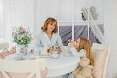 Πρόγευμα mom και κόρες Στις ίδιες πυτζάμες στοκ εικόνα