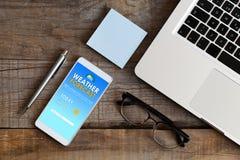 Πρόγνωση καιρού κινητό app σε μια τηλεφωνική οθόνη που τοποθετείται πέρα από ένα ξύλο Στοκ φωτογραφία με δικαίωμα ελεύθερης χρήσης