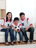 Πρόγονοι και ο γιος τους που προσέχουν ένα ποδόσφαιρο Στοκ φωτογραφία με δικαίωμα ελεύθερης χρήσης