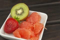 Πρόγραμμα διατροφής, ακατέργαστα τρόφιμα Ακτινίδιο, φράουλα και κόκκινο γκρέιπφρουτ σε ένα πιάτο πορσελάνης Στοκ Εικόνες