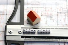 Πρόγραμμα καινούργιων σπιτιών με το κείμενο σπιτιών ονείρου για τον κυβερνήτη Σχέδιο αρχιτεκτονικής και μικρό πρότυπο σπίτι Στοκ εικόνες με δικαίωμα ελεύθερης χρήσης