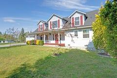 Πρόσοψη του αμερικανικού σπιτιού με τα κόκκινα παραθυρόφυλλα μια ηλιόλουστη ημέρα στοκ εικόνα