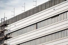Πρόσοψη του σύγχρονου κτηρίου με τα υλικά σκαλωσιάς στοκ φωτογραφίες με δικαίωμα ελεύθερης χρήσης