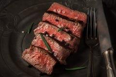 Πρόσφατα έτοιμο κόντρα φιλέτο βόειου κρέατος σε ένα σκοτεινό εκλεκτής ποιότητας πιάτο Στοκ φωτογραφία με δικαίωμα ελεύθερης χρήσης