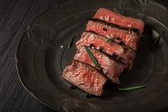 Πρόσφατα έτοιμο κόντρα φιλέτο βόειου κρέατος σε ένα σκοτεινό εκλεκτής ποιότητας πιάτο Στοκ Εικόνες