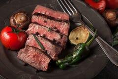 Πρόσφατα έτοιμο κόντρα φιλέτο βόειου κρέατος σε ένα σκοτεινό εκλεκτής ποιότητας πιάτο Στοκ φωτογραφίες με δικαίωμα ελεύθερης χρήσης
