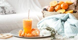 Πρόσφατα-αυξημένος οργανικός φρέσκος χυμός από πορτοκάλι στο εσωτερικό του σπιτιού, με ένα τυρκουάζ κάλυμμα και ένα καλάθι των φρ στοκ εικόνες με δικαίωμα ελεύθερης χρήσης