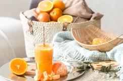 Πρόσφατα-αυξημένος οργανικός φρέσκος χυμός από πορτοκάλι στο εσωτερικό του σπιτιού, με ένα τυρκουάζ κάλυμμα και ένα καλάθι των φρ στοκ εικόνα