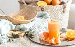 Πρόσφατα-αυξημένος οργανικός φρέσκος χυμός από πορτοκάλι στο εσωτερικό του σπιτιού, με ένα τυρκουάζ κάλυμμα και ένα καλάθι των φρ στοκ φωτογραφίες με δικαίωμα ελεύθερης χρήσης