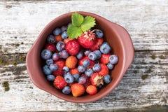 Πρόσφατα επιλεγμένες βακκίνια και φράουλες στον αγροτικό πίνακα Στοκ φωτογραφία με δικαίωμα ελεύθερης χρήσης