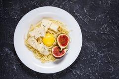 Πρόσφατα μαγειρευμένα ζυμαρικά με τα σύκα, λέκιθος αυγών, τυρί πέρα από έναν αγροτικό πίνακα πετρών Τοπ όψη διάστημα αντιγράφων Στοκ Εικόνα