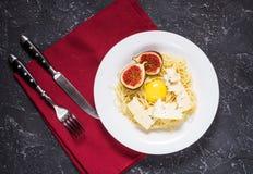 Πρόσφατα μαγειρευμένα ζυμαρικά με τα σύκα, λέκιθος αυγών, τυρί που διακοσμείται με την πετσέτα πέρα από έναν αγροτικό πίνακα πετρ Στοκ φωτογραφία με δικαίωμα ελεύθερης χρήσης