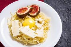 Πρόσφατα μαγειρευμένα ζυμαρικά με τα σύκα, λέκιθος αυγών, τυρί που διακοσμείται με την πετσέτα πέρα από έναν αγροτικό πίνακα πετρ Στοκ Εικόνα