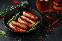 Πρόσφατα μαγειρευμένα λουκάνικα χασάπηδων στα δέρματα στο τηγανίζοντας τηγάνι χυτοσιδήρου με το μηλίτη μήλων οπωρώνων Sanford, De στοκ φωτογραφίες