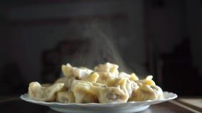 Πρόσφατα μαγειρευμένος σωρός του βρασίματος στον ατμό του pelmeni σε ένα πιάτο φιλμ μικρού μήκους