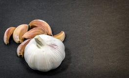 Πρόσφατα ξεφλουδισμένα γαρίφαλα σκόρδου μαζί με ολόκληρο ένα σκόρδο Στοκ Εικόνα