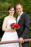 Πρόσφατα παντρεμένο ζευγάρι με τα κόκκινα τριαντάφυλλα στοκ εικόνες με δικαίωμα ελεύθερης χρήσης