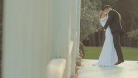 Πρόσφατα παντρεμένο ζευγάρι που φιλά και που αγκαλιάζει ήπια μέσα απόθεμα βίντεο