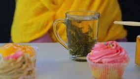 Πρόσφατα παρασκευασμένο πράσινο τσάι σε ένα διαφανές φλυτζάνι σε έναν γκρίζο πίνακα με τα κέικ απόθεμα βίντεο