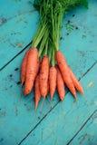 Πρόσφατα πλυμένα ολόκληρα καρότα στον παλαιό ξύλινο πίνακα στοκ φωτογραφίες