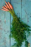 Πρόσφατα πλυμένα ολόκληρα καρότα στον παλαιό ξύλινο πίνακα στοκ φωτογραφία