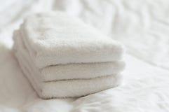 Πρόσφατα πλυμένες άσπρες πετσέτες χεριών που συσσωρεύονται σε ένα άσπρο κρεβάτι στοκ εικόνες με δικαίωμα ελεύθερης χρήσης