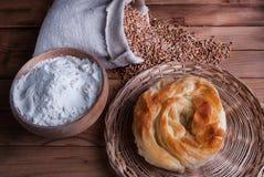 Πρόσφατα σπιτική πίτα με το τυρί και αλεύρι στα σιτάρια κύπελλων και σίτου στην τσάντα στον ξύλινο πίνακα στοκ φωτογραφία με δικαίωμα ελεύθερης χρήσης