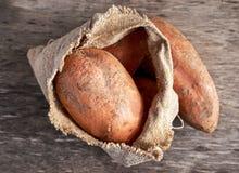 Πρόσφατα συγκομισμένες οργανικές γλυκές πατάτες σε μια burlap τσάντα στον ξύλινο πίνακα Στοκ Φωτογραφία