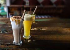 Πρόσφατα συμπιεσμένοι χυμός από πορτοκάλι και σοκολάτα milkshake ψηλά γυαλιά με ένα άχυρο σε έναν ξύλινο εκλεκτής ποιότητας πίνακ στοκ φωτογραφίες με δικαίωμα ελεύθερης χρήσης