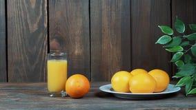Πρόσφατα συμπιεσμένος χυμός από πορτοκάλι σε ένα γυαλί Χύστε, συμπιέστε το χυμό από πορτοκάλι Σε μια ξύλινη ανασκόπηση φιλμ μικρού μήκους