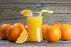 Πρόσφατα συμπιεσμένος χυμός από πορτοκάλι στο γυαλί με τα πορτοκαλιά φρούτα στο ξύλινο υπόβαθρο στοκ φωτογραφία με δικαίωμα ελεύθερης χρήσης