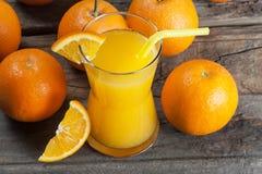 Πρόσφατα συμπιεσμένος χυμός από πορτοκάλι στο γυαλί με τα πορτοκαλιά φρούτα στο ξύλινο υπόβαθρο στοκ εικόνα με δικαίωμα ελεύθερης χρήσης