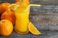 Πρόσφατα συμπιεσμένος χυμός από πορτοκάλι στο γυαλί με τα πορτοκαλιά φρούτα στο ξύλινο υπόβαθρο στοκ φωτογραφία