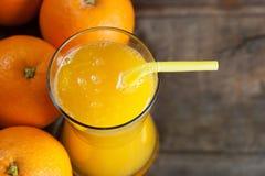 Πρόσφατα συμπιεσμένος χυμός από πορτοκάλι στο γυαλί με τα πορτοκαλιά φρούτα στο ξύλινο υπόβαθρο στοκ φωτογραφίες με δικαίωμα ελεύθερης χρήσης