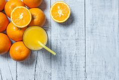 Πρόσφατα συμπιεσμένος χυμός από πορτοκάλι στο γυαλί με τα πορτοκαλιά φρούτα στο ξύλινο υπόβαθρο στοκ εικόνες