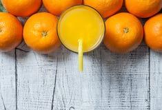 Πρόσφατα συμπιεσμένος χυμός από πορτοκάλι στο γυαλί με τα πορτοκαλιά φρούτα στο ξύλινο υπόβαθρο στοκ εικόνες με δικαίωμα ελεύθερης χρήσης