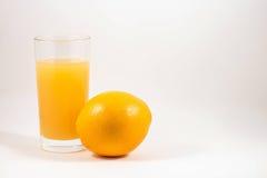 Πρόσφατα συμπιεσμένος χυμός από πορτοκάλι σε ένα γυαλί και ένα πορτοκάλι στοκ εικόνες