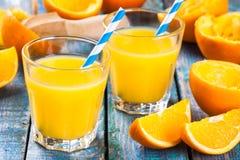 Πρόσφατα συμπιεσμένος χυμός από πορτοκάλι σε ένα γυαλί με τα άχυρα στοκ εικόνα