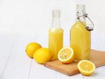Πρόσφατα συμπιεσμένος χυμός λεμονιών στο μπουκάλι και λεμόνια στο ελαφρύ υπόβαθρο Για το ποτό ή το κοκτέιλ βιταμινών στοκ εικόνες