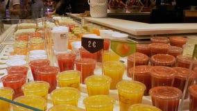 Πρόσφατα συμπιεσμένος χυμός στα πλαστικά εμπορευματοκιβώτια στην προθήκη Λα Boqueria Βαρκελώνη Ισπανία φιλμ μικρού μήκους