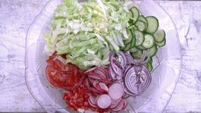 Πρόσφατα τεμαχισμένη θερινή σαλάτα Πολλά εύγευστα λαχανικά στη σαλάτα γυαλιού κυλούν - αγγούρι, μαρούλι, ραδίκι, ντομάτες, κόκκιν φιλμ μικρού μήκους