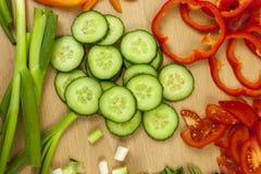 Πρόσφατα τεμαχισμένο αγγλικό αγγούρι που περιβάλλεται από άλλα λαχανικά Στοκ Φωτογραφία
